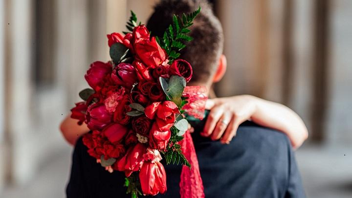 pareja-con-ramo-de-flores-rojas