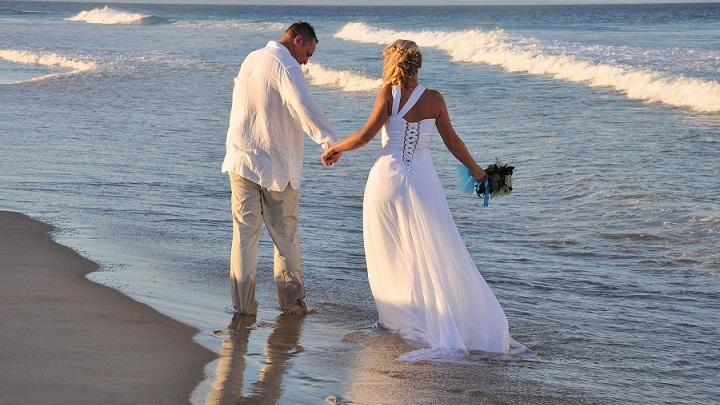 recien-casados-caminan-por-la-orilla-del-mar