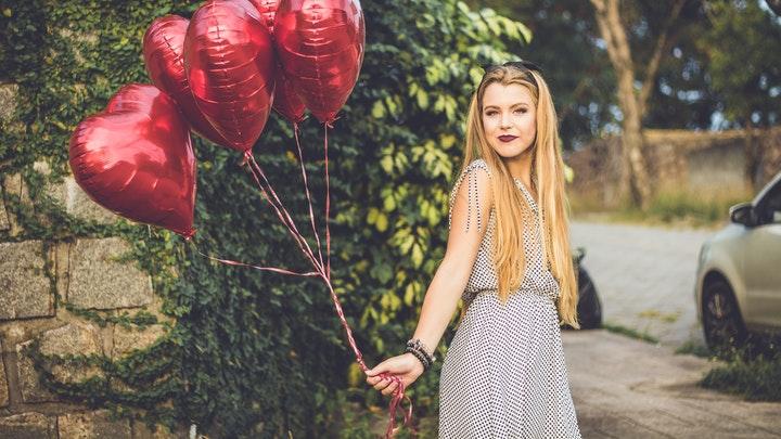 chica-con-globos-en-forma-de-corazon