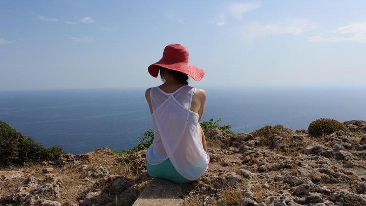 chica-con-sombrero-observa-el-horizonte
